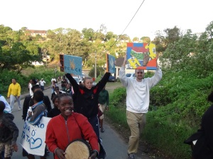 PPI-SA fellows Kristin Degou and Kyler McClary hold up peace-promoting artwork created by past PPI-SA participants as they march through Lamontville.