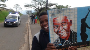 PPI-SA's Thobani Khumalo proudly displays a painting of Nelson Mandela that hangs in the PPI-SA office.