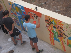 Onat, one of PPI-CY's young leaders works on the outdoor mural at The Home for Cooperation