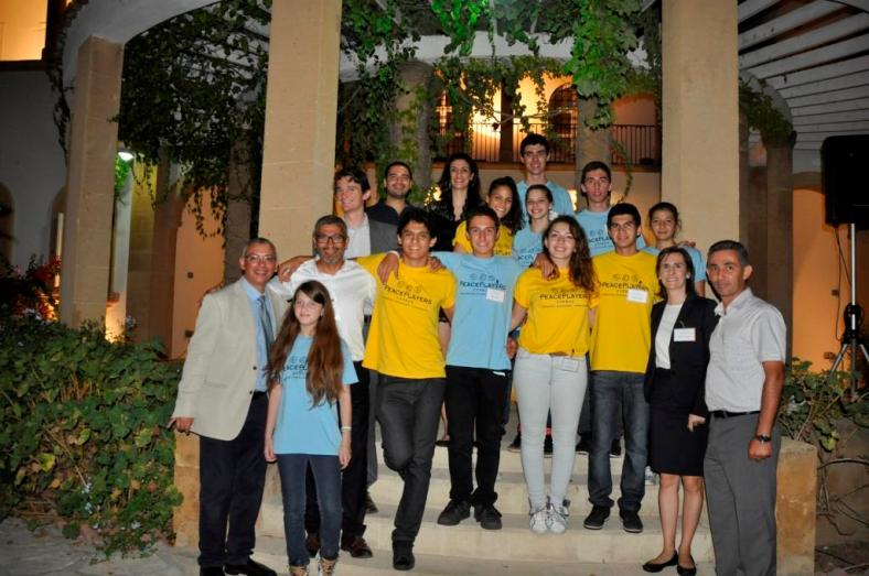 PeacePlayers-Cyprus Young Leaders take a break from serving at the Gala Dinner to take a photo on the steps of The British High Commission grounds with PeacePlayers and British High Commission representative Nick Kennedy