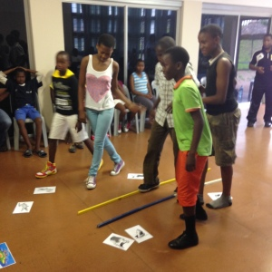 Players from Umlazi use a bridge to navigate obstacles and reach their goals in this life skills activity.