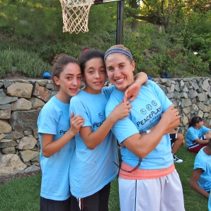 PeacePlayers' International Fellow Ashley Johnson posses with a few of her players from Iskele
