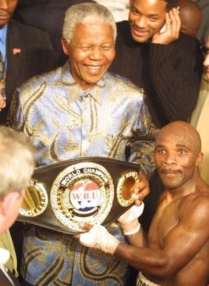 Baby Jake Matlala presents his world title belt to Nelson Mandela after his final fight in 2002. The two had mutual admiration for each other, and died two days apart this past week.