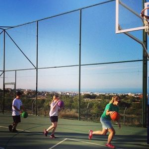 Coach Ashley shows kids a dribbling drill in Kyrenia