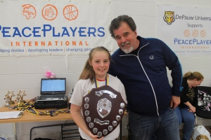 Professor and entertainment writer for esquire, Tom Chiarella presents the 'Player of the Year' award to Brooklyn O'Hare of the PPI-NI U13 girls team.