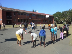 Ntuthuko (left) warming up with his Excelsior teammates with a fun ice-breaker before their game against Bhekaphambili Primary School