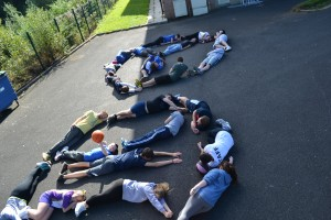 """PPI-NI Coaches and Champions4Peace participants forming body shapes to commemorate """"Peace Day"""""""