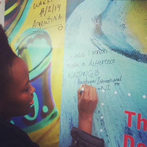 PPI-NI International Fellow, Nasiphi Khafu, signing a Peace Wall in North Belfast