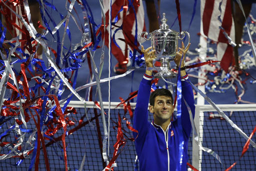 Novak Djokovic, of Serbia, holds up the championship trophy after defeating Roger Federer, of Switzerland, in the men's championship match of the U.S. Open tennis tournament, Sunday, Sept. 13, 2015, in New York. (AP Photo/Seth Wenig)